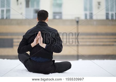 Man in black does yoga exercises on playground near building at winter day, back view