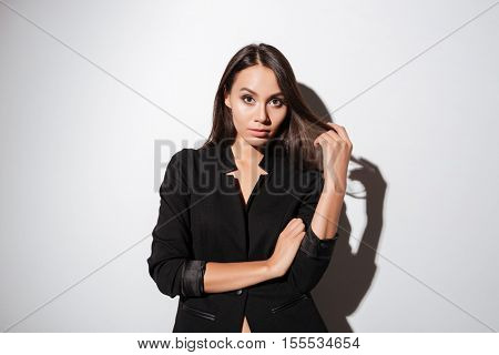 Portrait of a confident young woman in black suit standing and looking at camera over white background