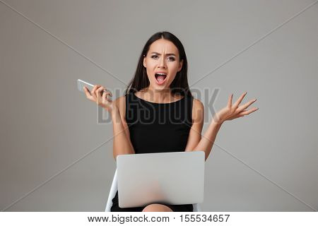 Upset angry woman in black dress screaming while sitting with laptop and mobile phone over gray background