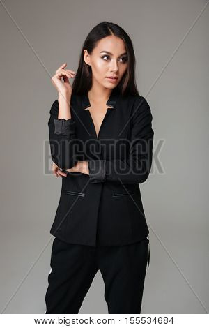 Young brunette business woman standing in black suit over gray background