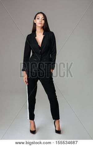 Full length portrait of a beautiful smart woman in black suit standing over gray background