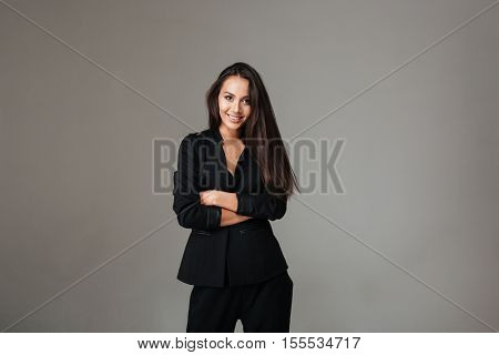 Smiling brunette woman in black suit standing with arms folded and looking at camera over gray background