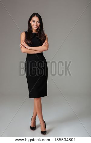 Lovely cute smiling young woman in black dress and shoes standing isolated on a gray background