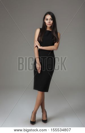 Full length portrait of a young woman standing in black dress isolated on a gray background