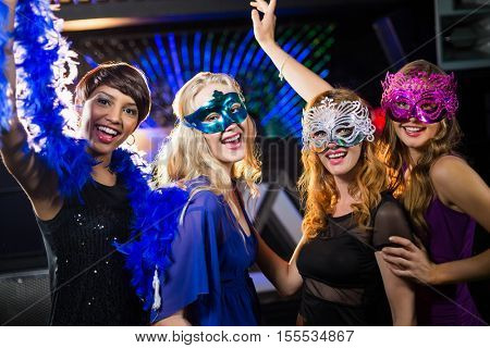Portrait of smiling female friends dancing on dance floor in bar