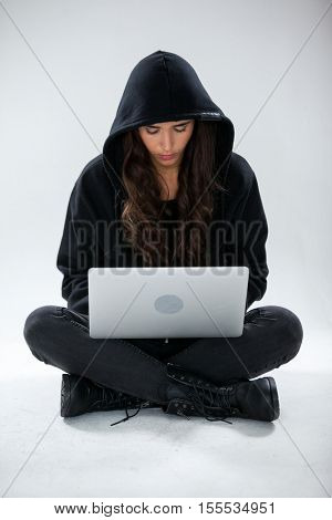 Hacker using a laptop against white background