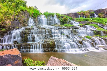 Pongour waterfall on summer days with many storied stone structure water flowing in the great stone steps. First waterfall in Lam Dong, Vietnam