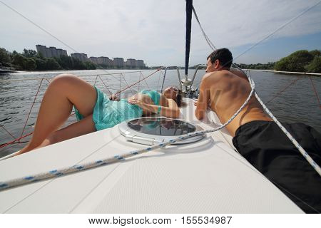 Man and woman lie on snout of yacht on river near city at summer day