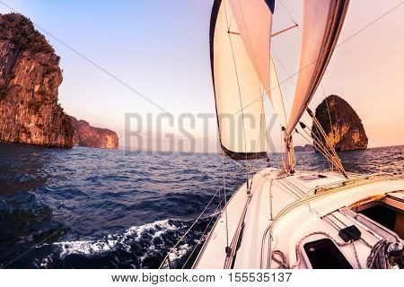 Sailing vessel moving in the sea with open sail at sunset