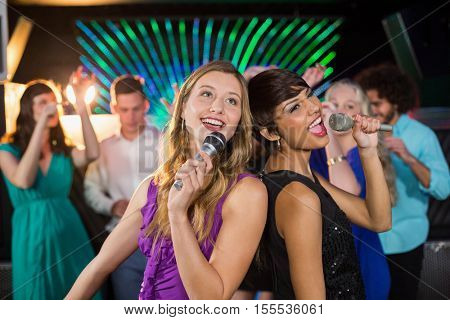 Two beautiful women standing back to back and singing song together in bar