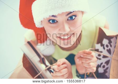Smiling woman in santa hat with many gift boxes on white background