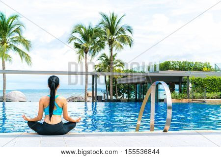 Portrait of young woman (fitness, yoga, perfect tanned body, healthy skin) at luxury swimming pool. Travel and Vacation. Freedom Concept. Outdoor shot