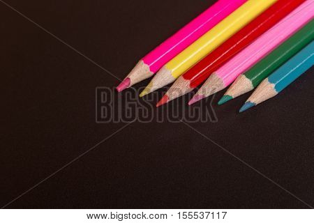 Wooden colorful pencils, on a dark background
