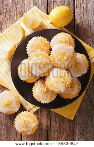 Sweet Lemon Muffins With Zest And Icing Sugar Close-up On A Plate. Vertical Top View