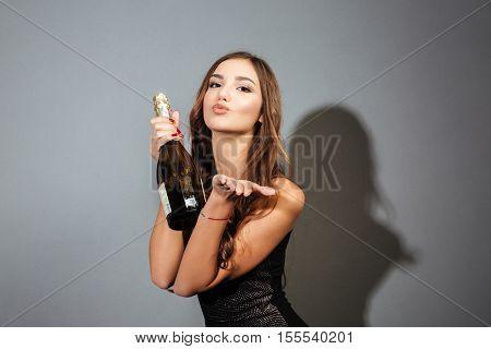 Model sends air kiss. holds bottle. gray background