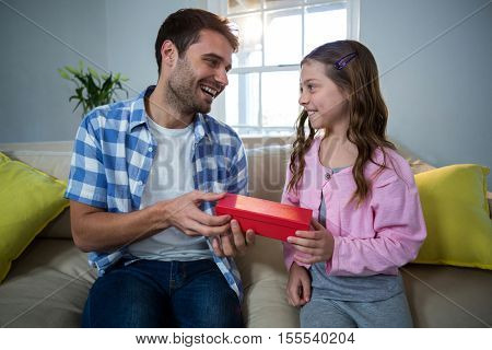 Father giving gift to daughter in the living room at home