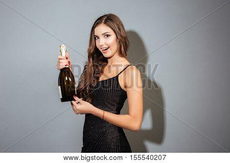 Beauty model with bottle. bottle of champagne. black dress