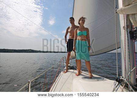 Man and woman stands on snout of white yacht on river at summer sunny day