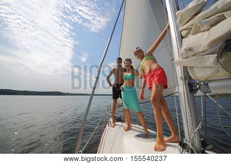 Father, mother and happy daughter sail on white yacht on river at summer sunny day