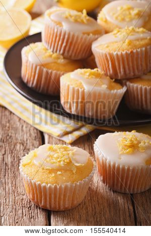 Homemade Lemon Muffins Sprinkled With Zest Close-up On A Plate. Vertical