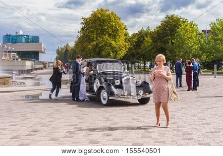 DNEPR UKRAINE - SEPTEMBER 24 2016:Scenery with fiance fiancee vintage car photographer and ordinary people on a Dnepr river embankment in center of Dnepr city at autumnal weekend at September 24,2016