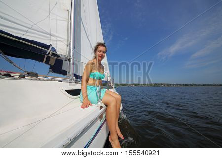 Barefoot woman sits on yacht during sailing on river at sunny summer day