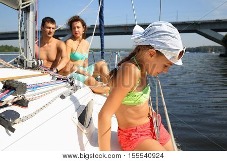 Father, mother and daughter sail on yacht on river at summer day, focus on child