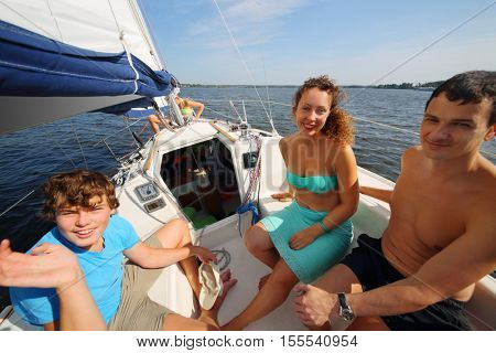 Father, mother and son sail on yacht on river at sunny day