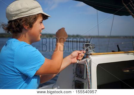 Boy teenager in cap controls boat during sailing on river at summer day