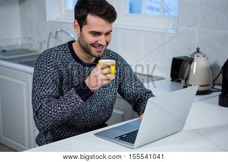 Man holding coffee mug while using laptop in the kitchen at home