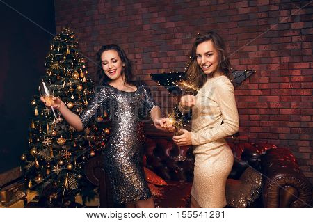 All The Best For The Coming Year! Two Young Women Dancing And Laughing With  Sparklers In Their Hand