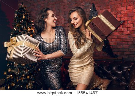 Two Beautiful Young Women Give Christmas Gifts And Dancing In Club
