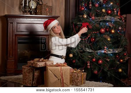 Young happy beautiful woman with gift boxes sits near Christmas tree in the room of the house.  Merry Christmas and New Year.