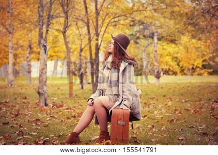 Beautiful young woman with suitcase in a autumn park