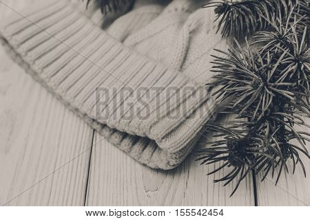 Winter composition with fir branches and white knitted hat.Black and white toned