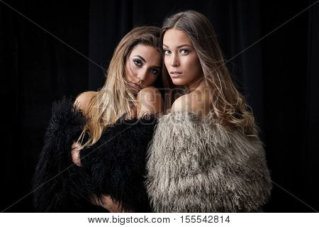 Two young ladies in fur coats posing on dark background