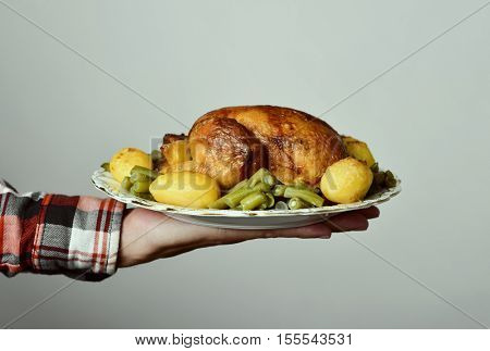 closeup of the hand of a young caucasian man holding a ceramic tray with a roast turkey served with potatoes and french beans