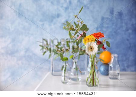 Flowers in vase on color background