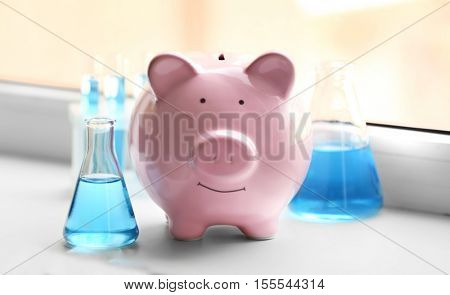 Pig money box and tubes with water on windowsill