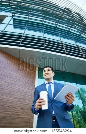 Young businessman holding disposable cup of coffee and tablet computer and looking away