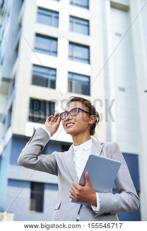 Beautiful Asian businesswoman admiring new building outside
