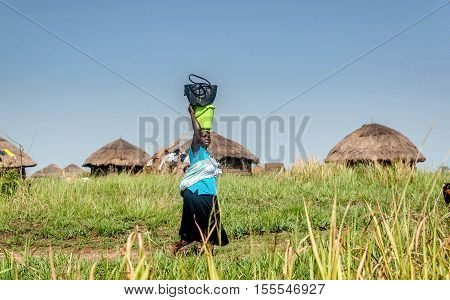 Uganda, Africa-  April 2, 2016: African woman carries load on her head in the Village in Uganda Africa