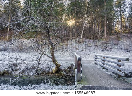 Frozen creek and wooden bridge - Winter image with a wooden bridge over a mountain creek in a frozen grass meadow near the forest