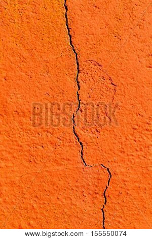 Surface of a red wall cracked by the passage of time