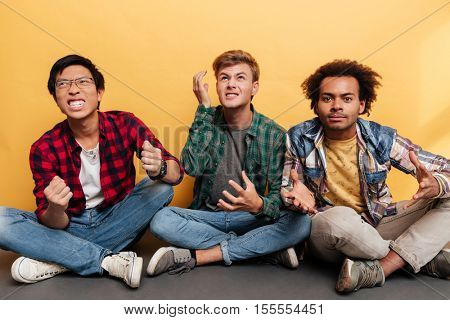 Three angry irritated young men friends sitting with legs crossed over yellow background