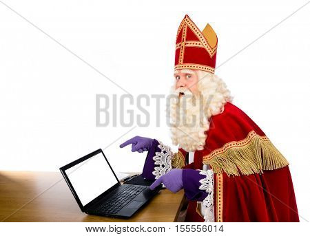 Sinterklaas pointing on laptop. isolated on white background. Dutch character of Santa Claus or saint nicholas