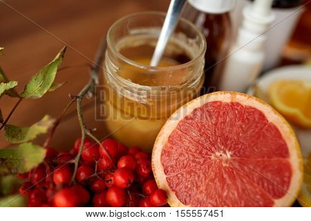 healthcare, traditional medicine and ethnoscience concept - grapefruit, honey with rowanberry and drugs