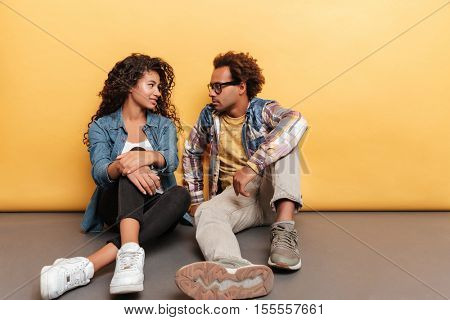Happy african american young couple sitting and talking over yellow background