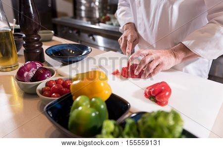Cutting the ingredient. Strong masculine big hands of the chef cutting a paper while being under the table in the kitchen of the restaurant and cooking