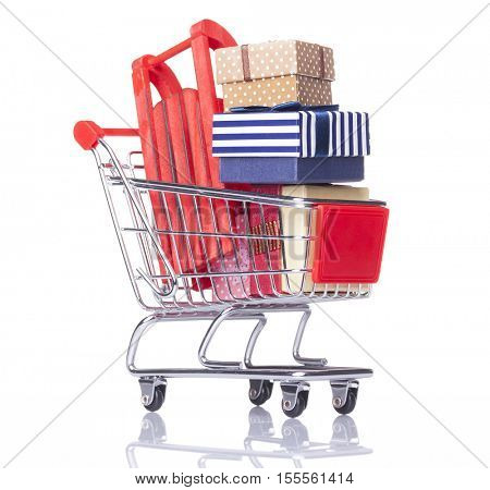 Closeup of a shopping cart with gift boxes and sled, isolated on white background